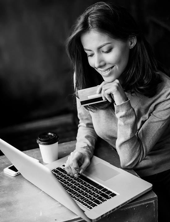 Women at coffee shop with laptop and credit card