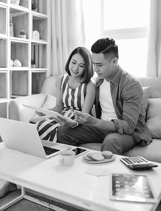 Asian couple at home sitting on couch reviewing documents