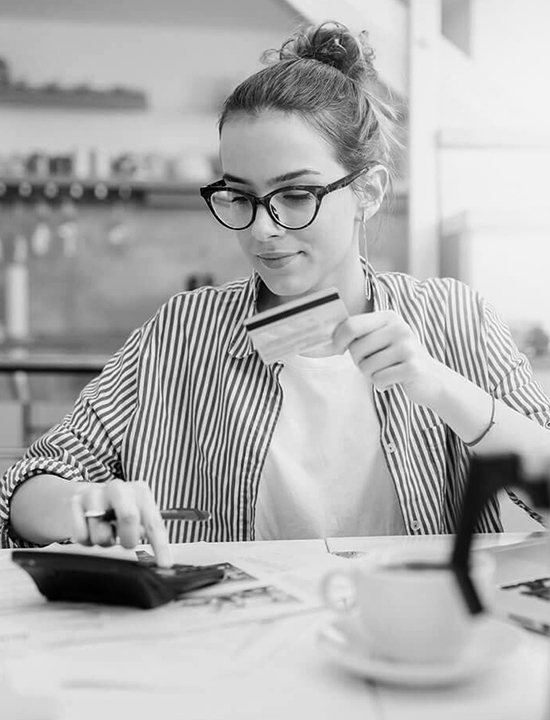 Girl with glasses with debit card and calculator