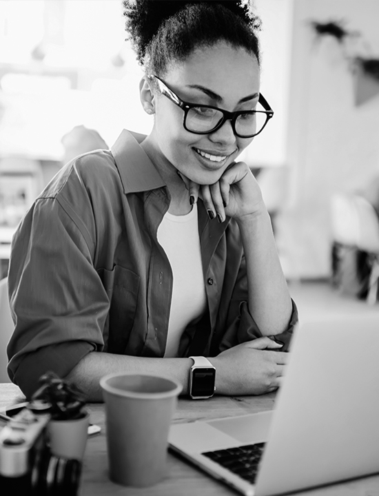 Girl with glasses looking at laptop with coffee