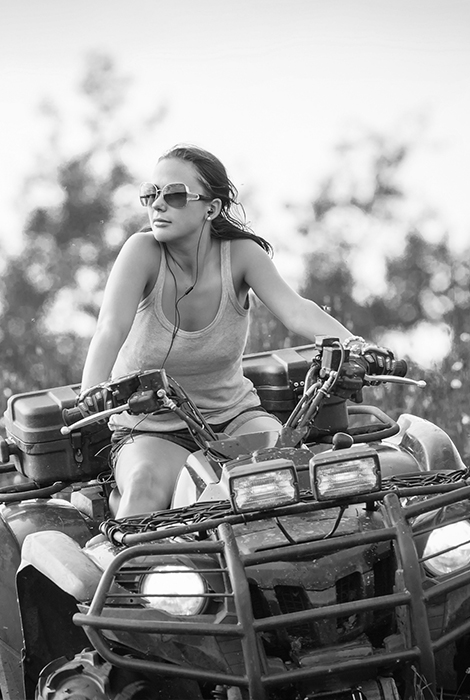 Women riding a four-wheeler with sunglasses on