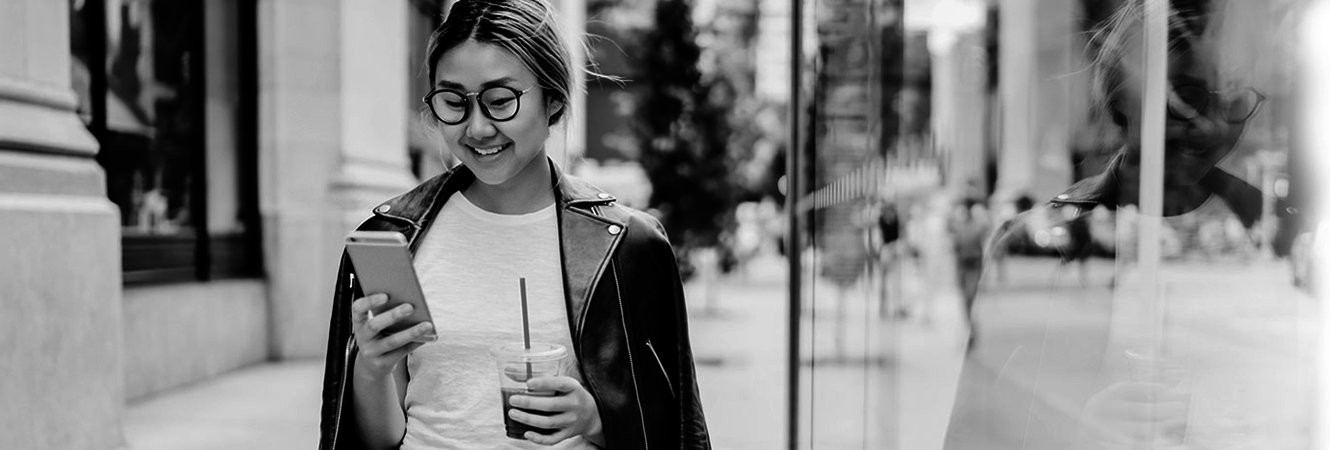 Young girl around town looking at smart phone with glasses and holding an iced coffee.